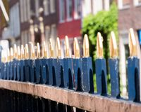 Rhythm of gilded fence posts in the Netherlands. An array of gold finished blue metal fence posts provide for an interesting photograph royalty free stock photos