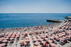 Free Rhythm Of Red Umbrellas And Tourists On A Sunny Beach In Genoa, Italy. Stock Image - 115970391