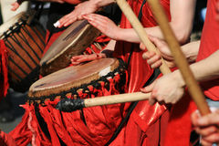 Rhythm in Red. Close up of red clad drums and the hands and sticks of musicians performing royalty free stock photo