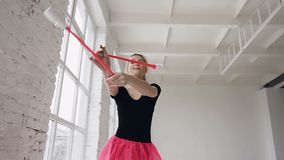 Rhythmic beautiful gymnast holding maces it makes acrobatic movements on white background in gymnastic hall. Girl. Dressed in black body and pink skirt. Slow stock footage
