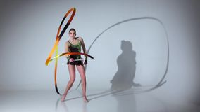 Rhythmic gymnast doing acrobatic moves with the tape. White background. Slow motion stock footage