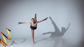 Rhythmic gymnast doing acrobatic moves with the tape. White background. Slow motion stock video footage