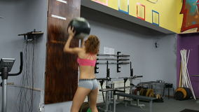 Rhythmic gymnast doing exercise with ball in gym. Girl throws a heavy ball stock footage