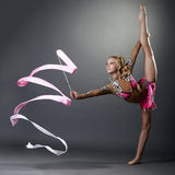 Rhythmic gymnast doing vertical split with ribbon Stock Photo