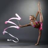 Rhythmic gymnast doing vertical split with ribbon. On grey background stock photo