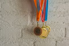Rhythmic gymnastics medals hanging in front of a white brick wall, sport achievements. Some rhythmic gymnastics medals hanging in front of a white brick wall stock photos
