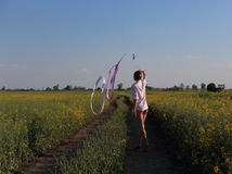 Rhythmic gymnastics woman with red tape. Gymnastics in the field, village Royalty Free Stock Photo
