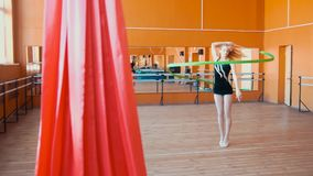 Rhythmic gymnastics - young woman training a gymnastics exercise with a green ribbon. Wide angle stock photos