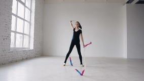 Rhythmische Gymnastik des blonden Jugendlichetanzes, modern mit farbigem Band im schwarzen Körper im weißen Hintergrund am Sport stock video