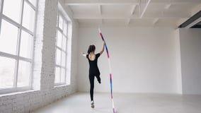 Rhythmische Gymnastik des blonden netten Mädchens, modern mit farbigem Band im schwarzen Bodysuit herein zuhause am weißen bacgro stock footage