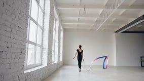 Rhythmische Gymnastik des blonden netten Mädchentanzes, modern mit farbigem Band im schwarzen Bodysuit vor den Fenstern stock video footage