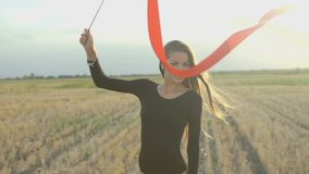 Rhythmische Gymnastik des jungen Brunettefrauentanzes, modern mit rotem Band stock video