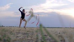 Rhythmische Gymnastik des jungen Brunettefrauentanzes, modern mit rotem Band stock video footage