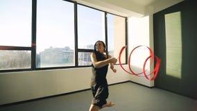 Rhythmische Gymnastik des Tanzes der jungen Frau des Brunette, modern mit rotem Band im schwarzen sexy Kleid vor den Fenstern Sun stock footage