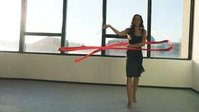Rhythmische Gymnastik des Tanzes der jungen Frau des Brunette, modern mit rotem Band im schwarzen sexy Kleid vor den Fenstern Sun stock video footage