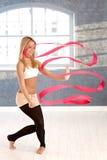 Rhytmic gymnast som övar med bandet Arkivbilder