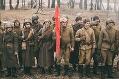 Ri--enactors vestito come soldati sovietici russi della fanteria della seconda guerra mondiale che stanno nella fila fotografia stock