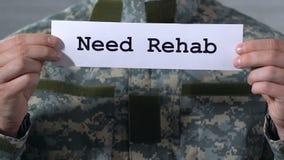 Riabilitazione di bisogno scritta su carta in mani del soldato maschio, aiuto ai veterani di guerra archivi video
