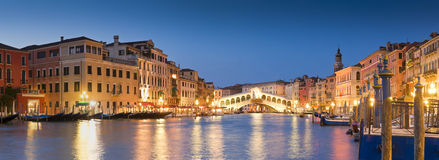 Rialto Bridge, Venice. Pretty night time illuminations of the iconic Rialto Bridge (1591) and Venetian Villas over the grand canal in Venice. Stitched panoramic Royalty Free Stock Images