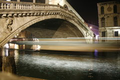 Rialto Zoom. A Vaporetto passing under the Rialto Bridge at night Royalty Free Stock Photos