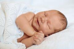 Riant, souriant peu de bébé garçon nouveau-né dormant dans le bla blanc images stock