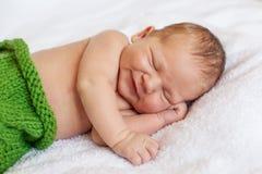 Riant, souriant peu de bébé garçon nouveau-né dormant dans le bla blanc photographie stock