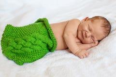 Riant, souriant peu de bébé garçon nouveau-né dormant dans le bla blanc photos stock