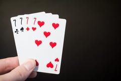Riassunto: equipaggi la carta da gioco quattro sette della tenuta della mano isolati su fondo nero con copyspace Immagine Stock Libera da Diritti