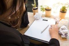 Riassunto sollecitato di scrittura della donna di affari su carta ai wi di legno dello scrittorio Fotografie Stock
