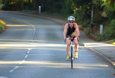 Riathlon competitor on road cycling stage of competition. Royalty Free Stock Photos