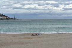 Riazor Beach with young people taking a break. Rainy day, cloudy grey sky. La Coruna, Spain. royalty free stock photography