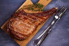 Rib Eye Beef Steak med timjan på skärbräda arkivfoto