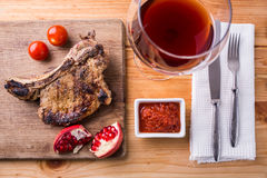 Rib eye steak on chopping board with glass of wine Stock Images