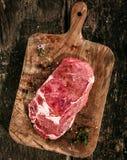 Rib Eye Steak crudo en tabla de cortar de madera rústica Imágenes de archivo libres de regalías