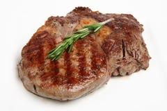 Rib-Eye Steak Dinner. Close-up of a freshly griddled rib-eye steak resting on a white plate Royalty Free Stock Image