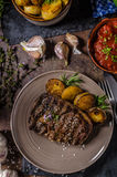 Rib eye steak. With herbs, roasted potatoes, hot tomato garlic sauce and herbs stock photo