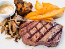 Rib eye steak meal with french fries and mushroom Stock Image