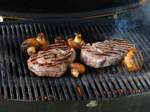Rib eye steak and mushrooms on the grill Royalty Free Stock Photo
