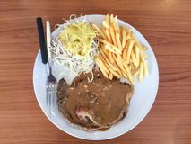 Rib-eye steak with pepper sauce, French Fries and salad royalty free stock photography