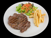 Rib eye steak served with french fries and salads to vegetables isolated on the black background with clipping path Royalty Free Stock Photography