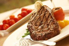 Rib Eye Steak served with wine. 12oz ribeye steak topped with truffle butter and grilled tomato royalty free stock photos