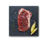 Rib eye steak with spices on slate isolated. Raw rib eye steak with herb, lemon and spices on slate isolated on white background. Cooking ingredients for Royalty Free Stock Image