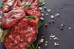 Rib eye steak and spices on wood at black background Stock Photography