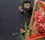 Rib eye steak and spices on wood at black background. Raw rib eye steak with herbs and spices. Cooking ingredients for restaurant dish. Fresh meat, pepper salt Stock Photos