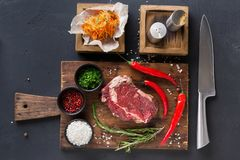 Rib eye steak with spices on wooden desk with russian korean salad Royalty Free Stock Photo
