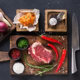Rib eye steak with spices on wooden desk with russian korean salad Royalty Free Stock Photography