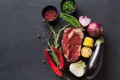 Rib eye steak and vegetables on plate at black background Royalty Free Stock Images