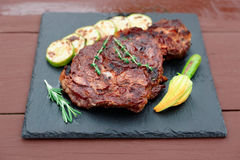 Rib eye steak with vegetables on slate plate Stock Images
