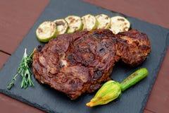 Rib eye steak with vegetables on slate plate Royalty Free Stock Photo