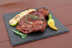 Rib eye steak with vegetables on slate plate Royalty Free Stock Images